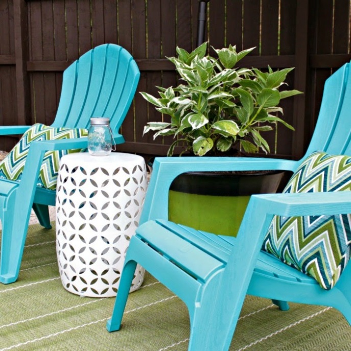 brightly colored adirondack chairs look great against a dark fence