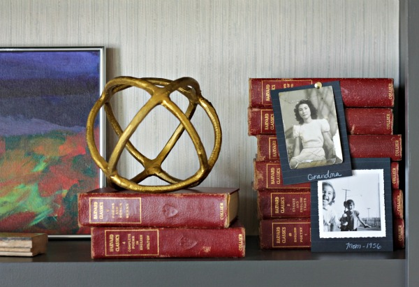 Use a stack of books to display old black and white photos with a thumbtack